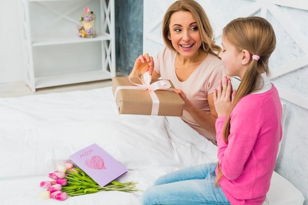 Madre e figlia che si siedono sul letto con il regalo Foto Gratuite
