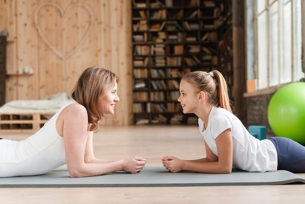 Madre e figlia che si siedono sulla stuoia che se lo esamina Foto Gratuite