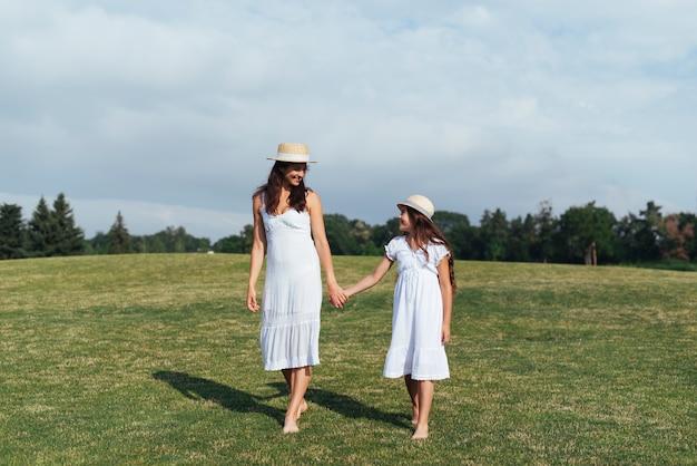 Madre e figlia che si tengono per mano all'aperto Foto Gratuite