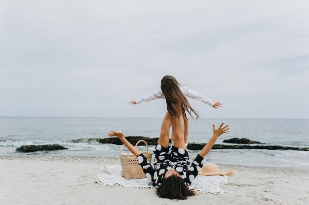 Madre e figlia che si tengono per mano e che camminano sulla spiaggia. Foto Premium