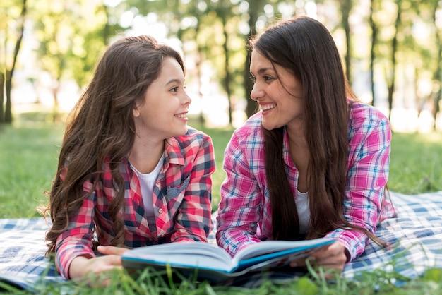 Madre e figlia che si trovano sull'erba che se lo esaminano mentre tenendo libro in parco Foto Gratuite