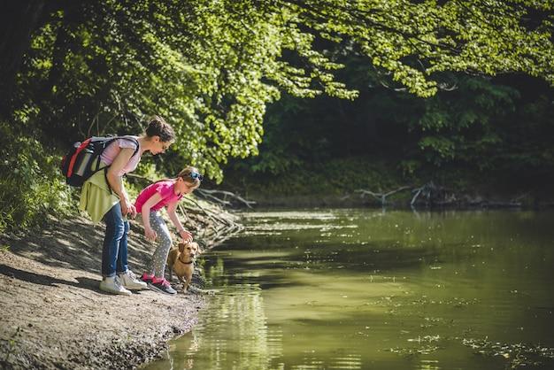 Madre e figlia con cane sul lago Foto Premium