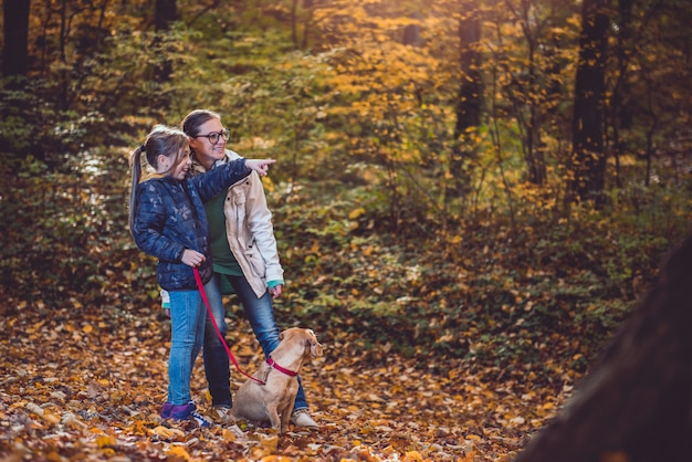 Madre e figlia con il cane che fa un'escursione in una foresta Foto Premium