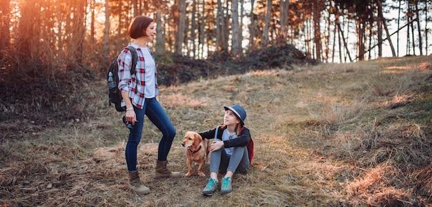 Madre e figlia con il cane nella foresta durante il tramonto Foto Premium
