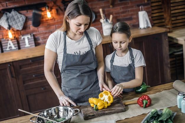 Madre e figlia con peperoni sulla cucina Foto Premium