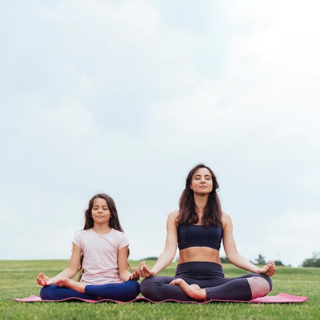 Madre e figlia di vista frontale che meditano all'aperto Foto Gratuite