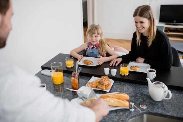 Madre e figlia facendo colazione vicino a padre Foto Gratuite