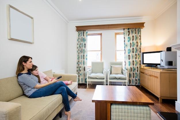 Madre e figlia guardare la tv in salotto Foto Gratuite