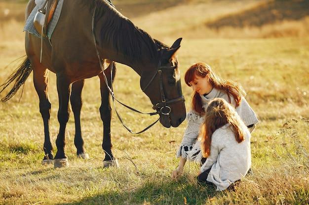 Madre e figlia in un campo che gioca con un cavallo Foto Gratuite
