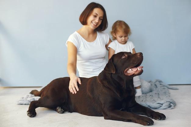 Madre e figlia piccola che giocano con il cane a casa Foto Gratuite