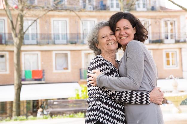 Madre e figlia positive felici che stanno per macchina fotografica Foto Gratuite