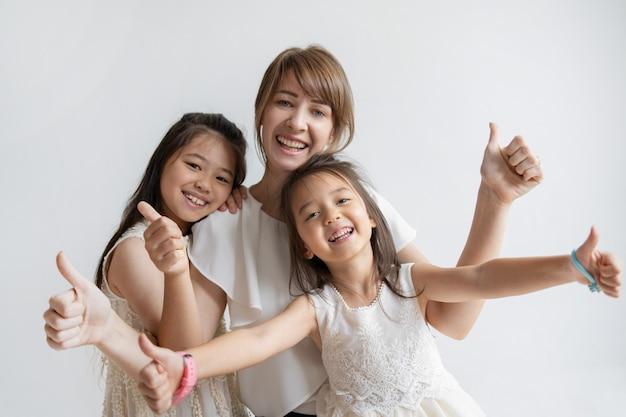 Madre e figlie caucasiche positive che mostrano i pollici in su Foto Gratuite