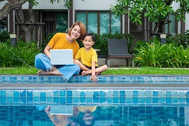 Madre e figlio asiatici felici che per mezzo del computer portatile alla piscina all'aperto Foto Premium