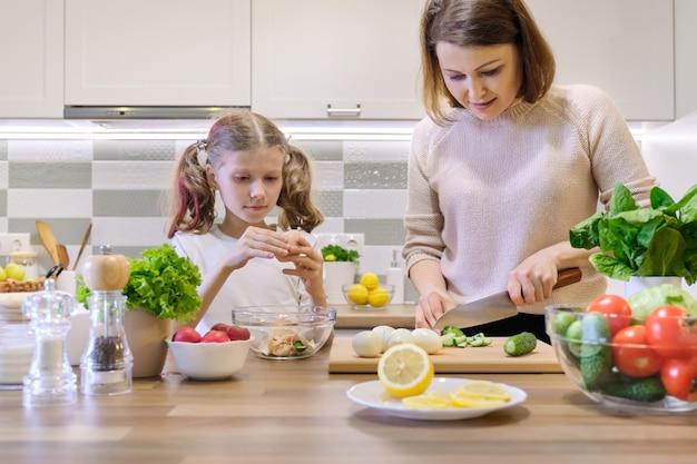 Madre e figlio che cucinano insieme a casa in cucina Foto Premium