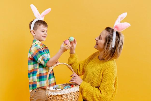 Madre e figlio dell'angolo alto con le uova dipinte Foto Gratuite