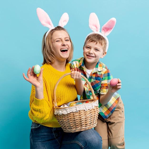 Madre e figlio felici con la merce nel carrello dipinta delle uova Foto Gratuite