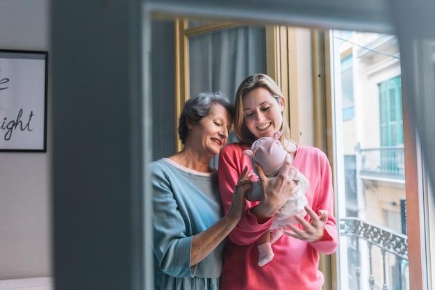 Madre e nonna guardando il bambino Foto Gratuite