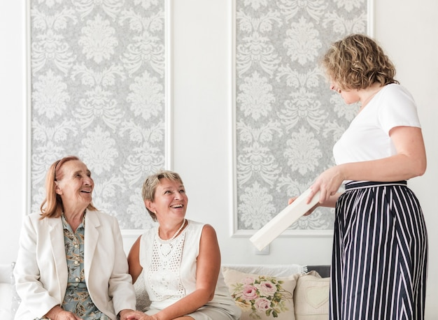 Madre e nonna guardando la loro figlia tenendo album fotografico a casa Foto Gratuite