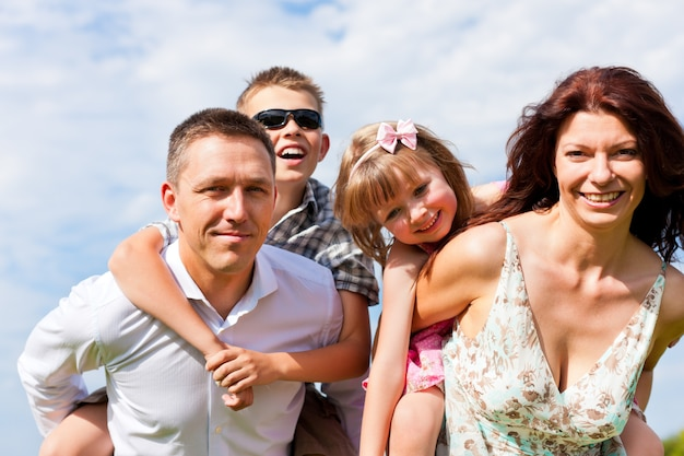 Madre e padre che trasportano i bambini sulle spalle Foto Premium