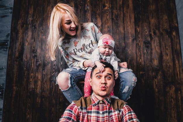Madre e padre con il loro bambino in una sedia bar contro lo sfondo di una parete di legno Foto Premium