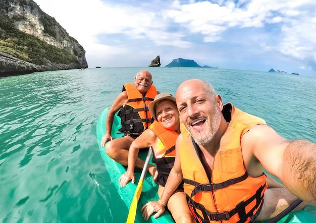 Madre e padre senior felici con il figlio che prende selfie all'escursione del kajak in tailandia Foto Premium