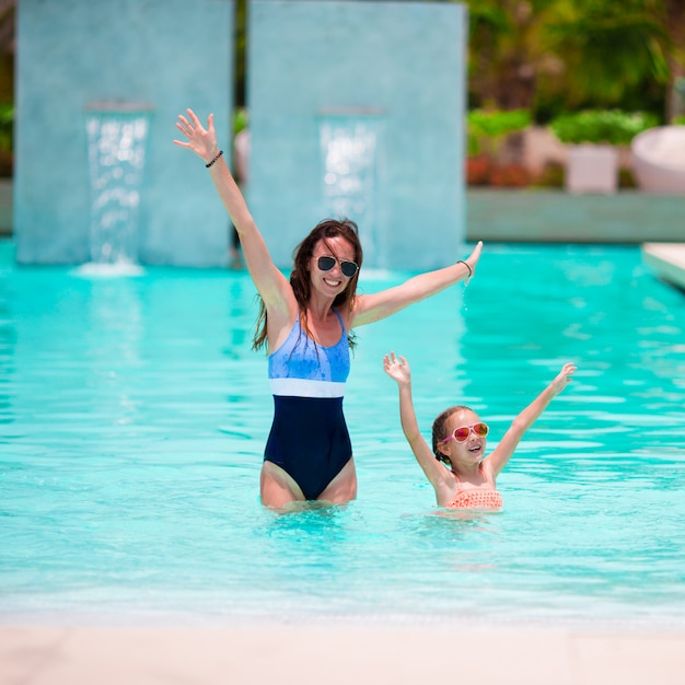 Madre e ragazza che godono le vacanze estive nella piscina di lusso Foto Premium