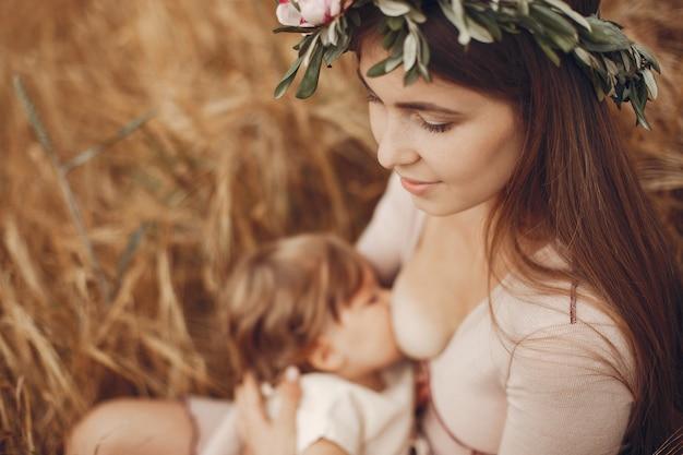 Madre elegante con la piccola figlia sveglia in un campo Foto Gratuite