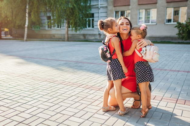 Madre felice che incontra le sue figlie dei bambini dopo le lezioni Foto Premium