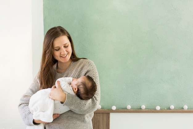 Madre felice che tiene bambino sveglio tra le braccia Foto Gratuite