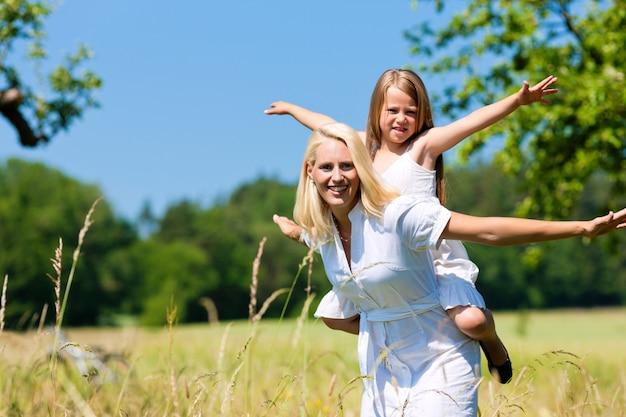 Madre felice che trasporta la sua figlia sulle spalle nella natura Foto Premium