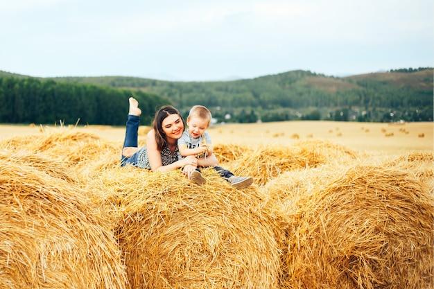 Madre felice con il figlio in estate al pagliaio del campo e della paglia Foto Premium