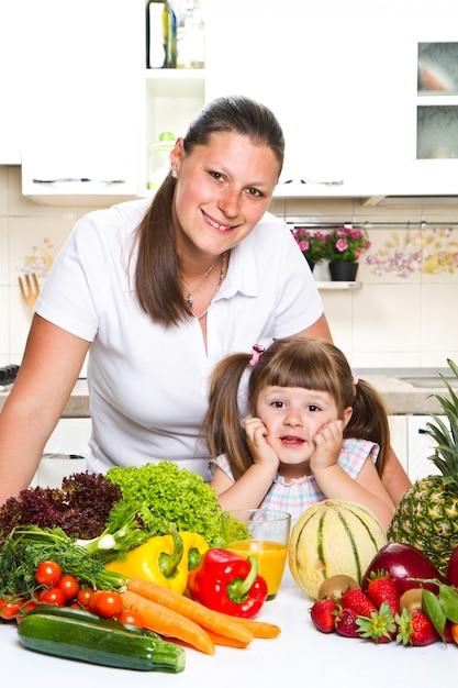 Madre felice e figlia che sorridono nella cucina Foto Premium