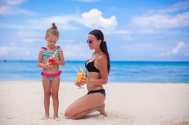 Madre felice e la sua piccola figlia adorabile con succo alla spiaggia tropicale Foto Premium