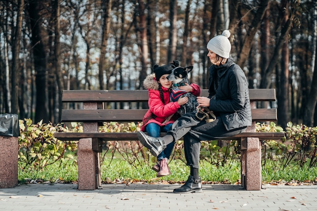 Madre felice e sua figlia con il cane che riposa su una panchina Foto Gratuite