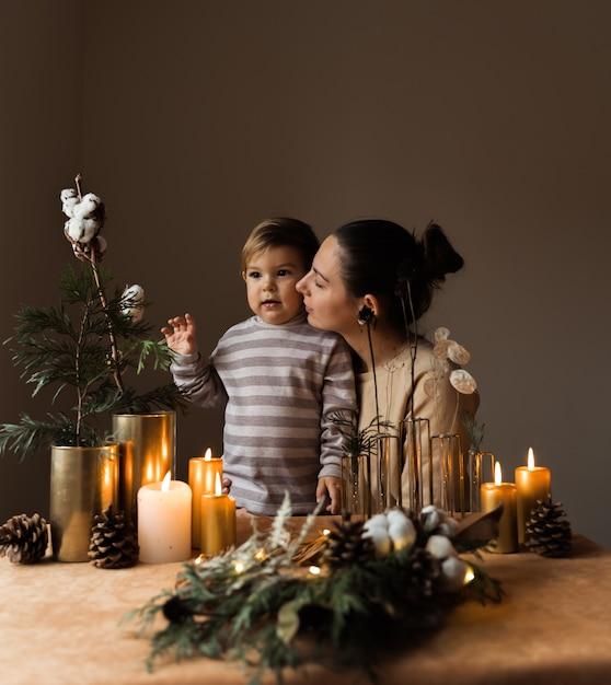 Madre felice e suo figlio con decorazioni natalizie. casa accogliente hygge. felice momento della maternità Foto Premium
