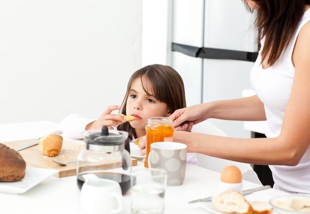 Madre graziosa che dà il pane tostato con marmellata a sua figlia per la prima colazione Foto Premium