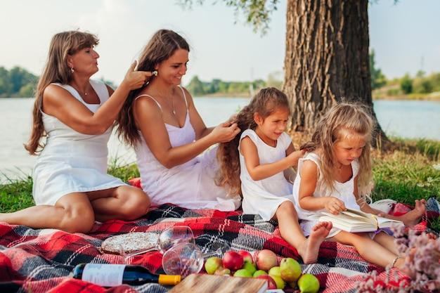 Madre, nonna e bambini che intrecciano le trecce. famiglia divertendosi durante il picnic nel parco. tre denerazioni Foto Premium