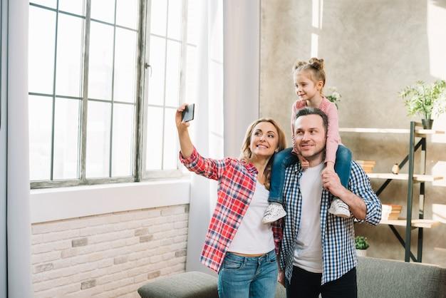 Madre prendendo selfie sul cellulare con il marito e la figlia Foto Gratuite