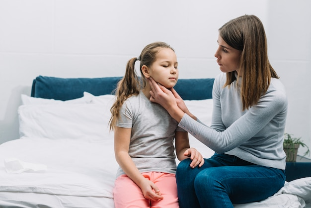 Madre seduta con sua figlia che le tocca la gola e il collo Foto Gratuite