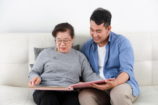 Madre senior asiatica della donna e figlio del giovane in camicia blu che guarda l'album di foto e che parla il fronte felice di sorriso in salone Foto Premium