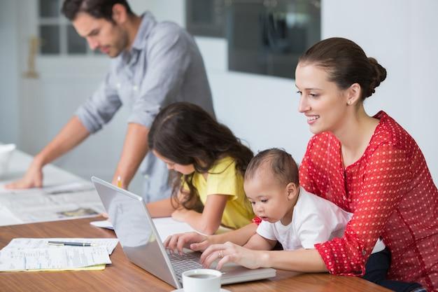 Madre sorridente che lavora al computer portatile con il bambino mentre studio della figlia Foto Premium