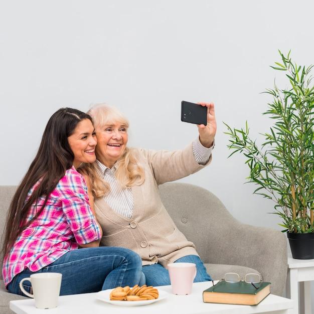 Madre sorridente e la sua giovane figlia che prendono selfie sul telefono cellulare a casa Foto Gratuite