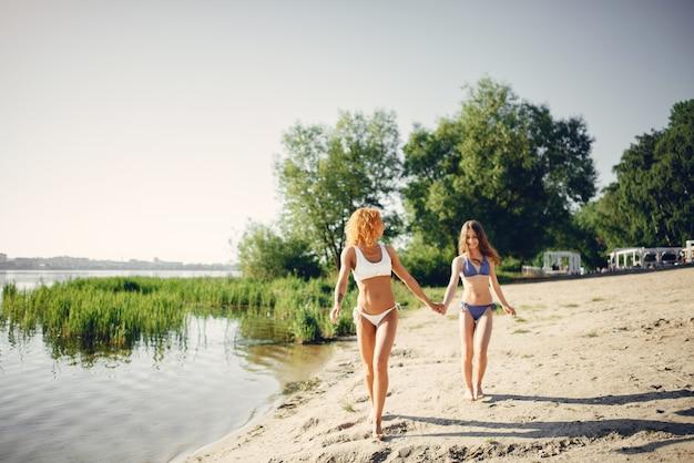 Madre sportiva con la figlia sveglia che cammina vicino al lago Foto Gratuite