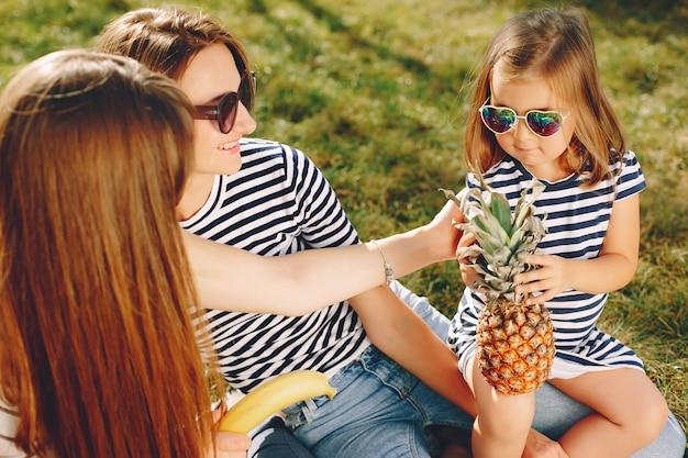 Madri con bambini che giocano in un parco estivo Foto Gratuite