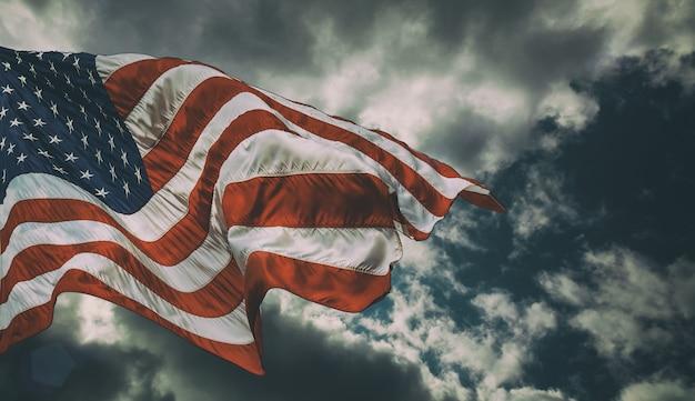 Maestosa bandiera degli stati uniti contro uno sfondo scuro Foto Premium