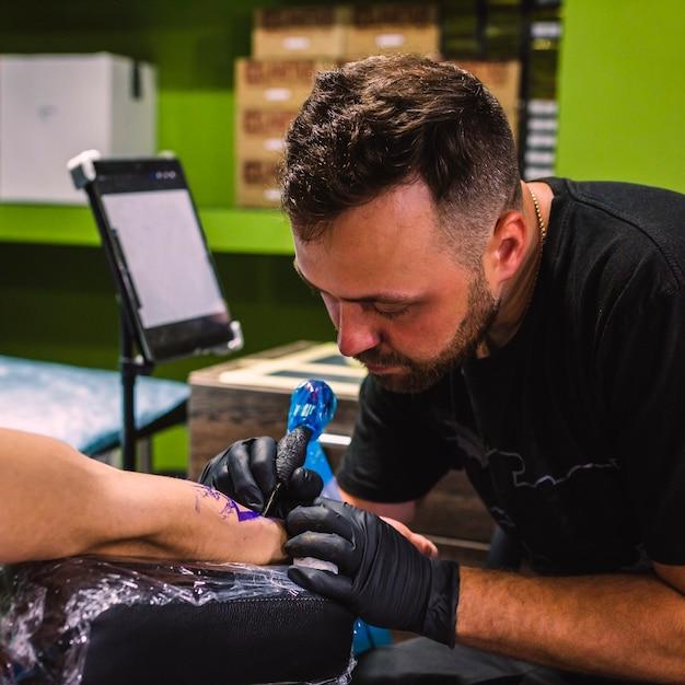 Maestro che fa tatuaggio con la macchina dell'ago Foto Gratuite