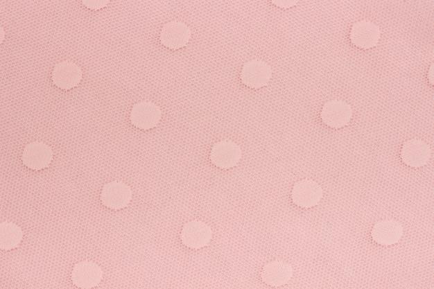 Maglia di tessuto decorativo rosa con motivi di cerchi come sfondo o texture. Foto Premium