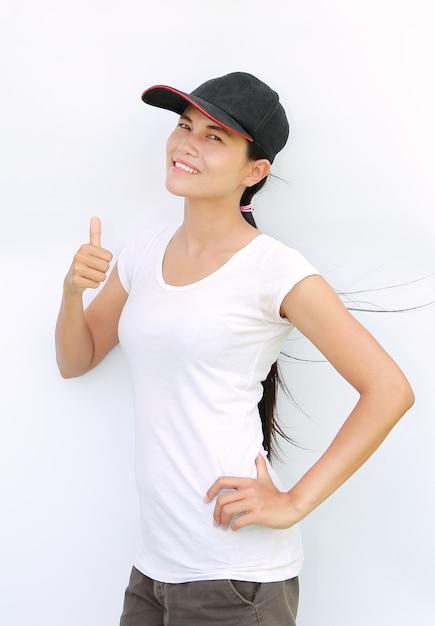 Maglietta e protezione asiatiche di usura di donna che mostrano pollice in su su priorità bassa bianca Foto Premium