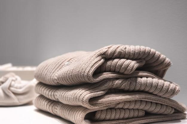 Maglioni beige realizzati con tessuti naturali sono ripiegati sul tavolo. Foto Premium