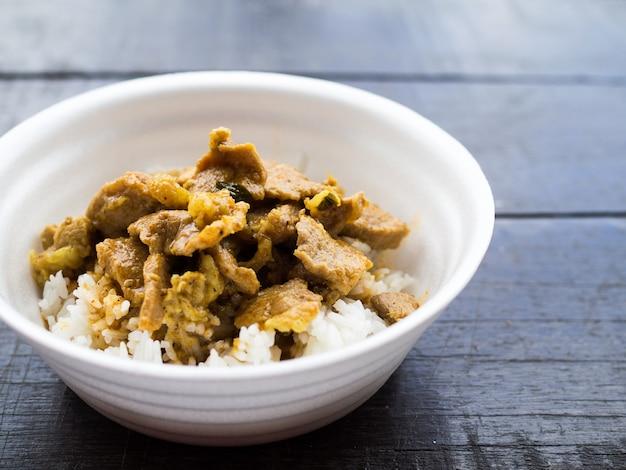 Maiale al curry rosso con riso in tazza di schiuma Foto Premium